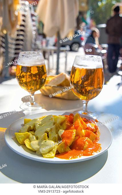 Platter of alioli potatoes and bravas potatoes with two glasses of beer in a terrace. Spain
