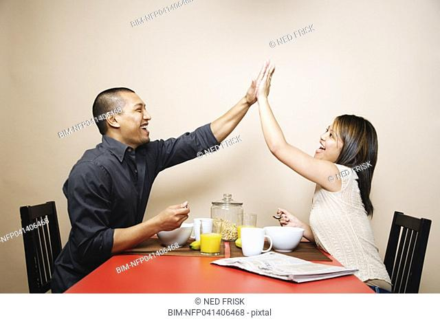 Asian couple high-fiving at breakfast table