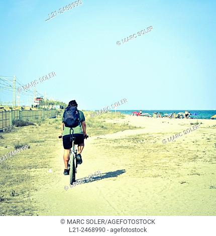 Summer concept. A man goes by bicycle to the beach. Maresme, Barcelona province, Catalonia, Spain