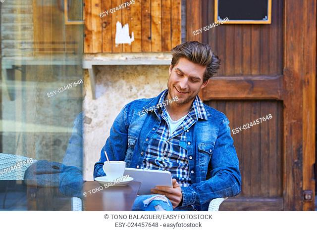 Young man with tablet pc touch in an cafe outdoor having some coffe cup