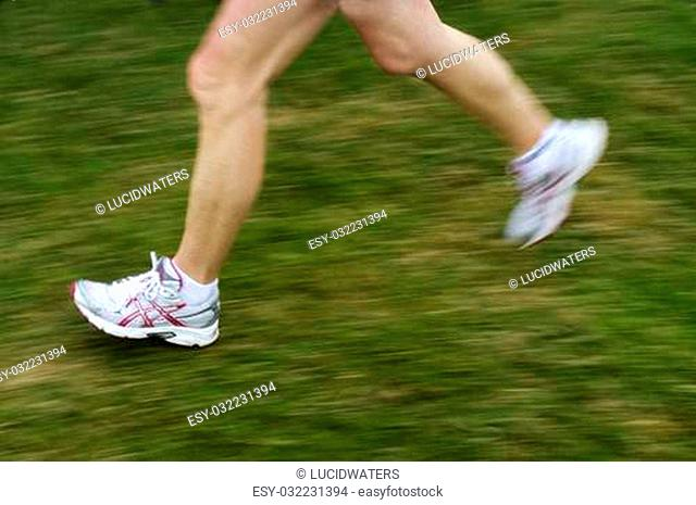 Running sport. Man runner legs and shoes in action on green grass outdoors during a Marathon running. Male athlete model
