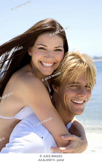 Man giving girlfriend piggyback ride at beach