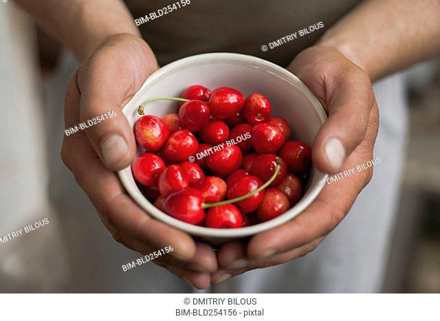 Hands of woman holding a bowl of cherries