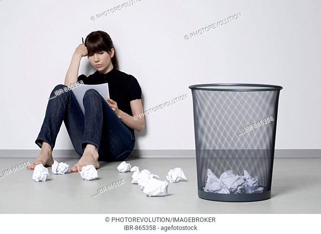 Young, dark-haired woman sitting on the floor leaning against a wall amongst screwed-up balls of paper, deliberating