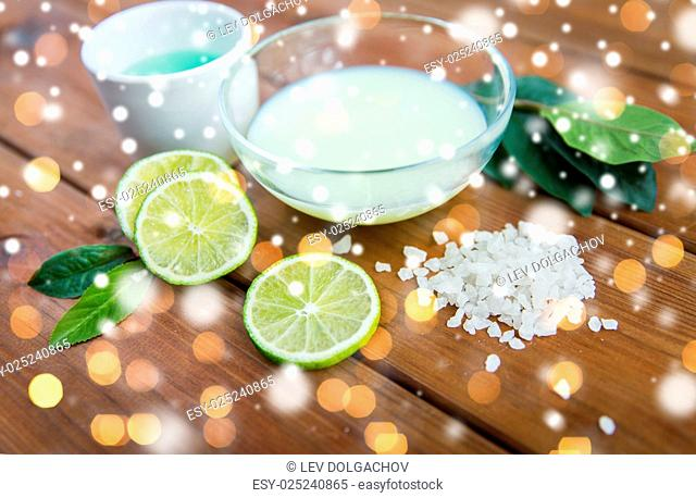 beauty, spa, bodycare and natural cosmetics concept - bowls with citrus body lotion, cream and sea salt on wood over lights and snow