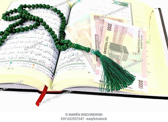 aufgeschlagener Koran mit iranischem Rial