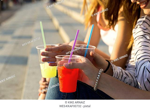 Three young women with soft drinks, partial view