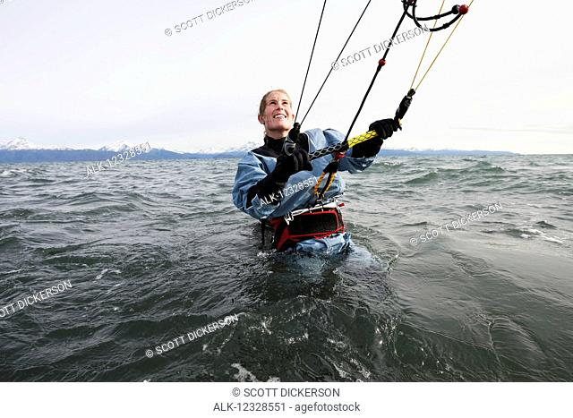 Woman in the water preparing to kitesurf, Kachemak Bay, South-central Alaska, USA