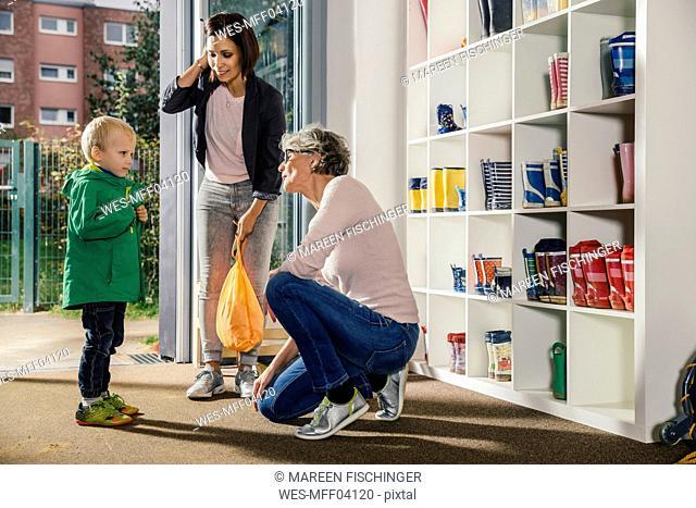 Boy with mother and pre-school teacher in kindergarten