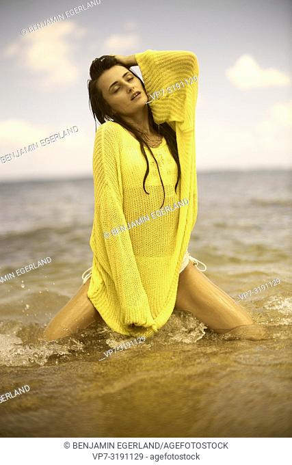 Portrait of woman at the beach, wearing a yellow sweater. Crete, Greece