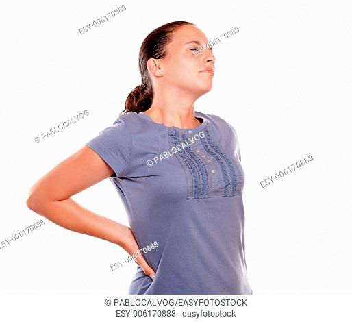 Unhappy young woman with a terrible back pain standing over white background
