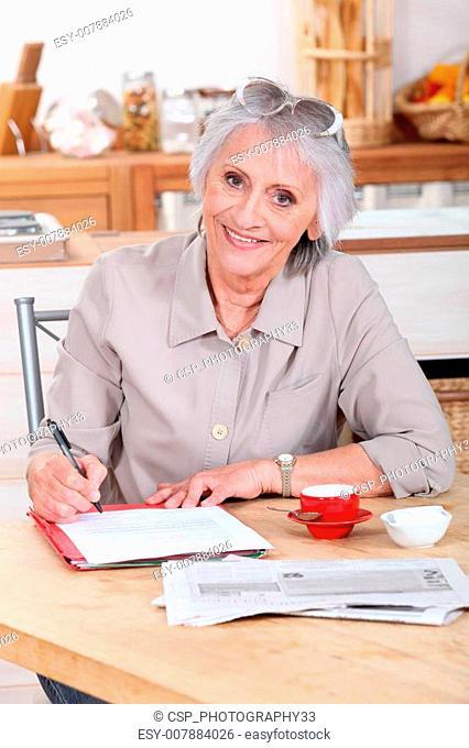 a senior woman writing a letter