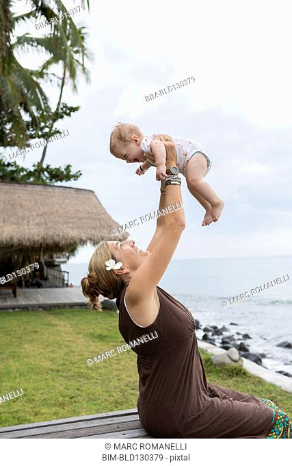 Caucasian mother and baby playing outdoors