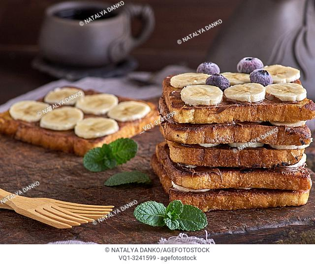 large sandwich of toasted square pieces of white bread, in the middle of chocolate and banana slices, a French toast on a brown wooden board