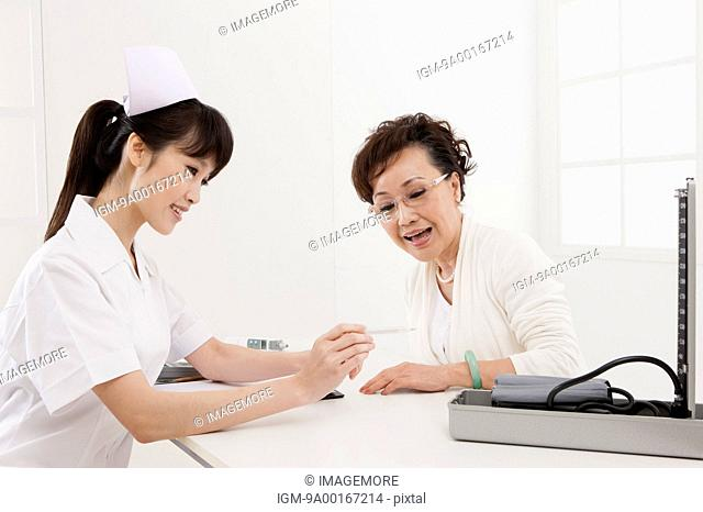 Senior woman making medical exam and looking away with smile