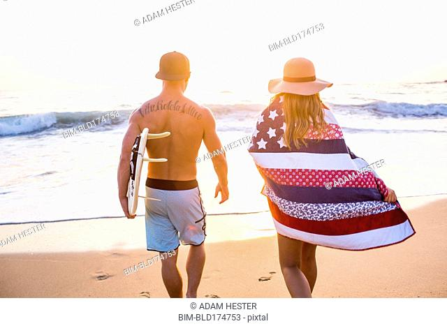 Caucasian couple walking on beach