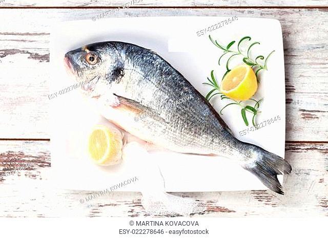 Sea bream with lemon on white tray