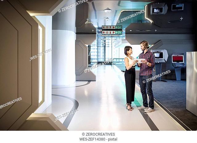 Business people discussing in an office corridor