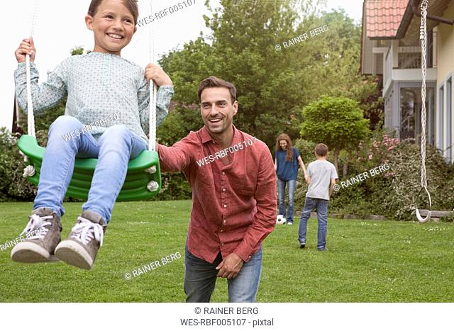 Father pushing daughter on swing in garden
