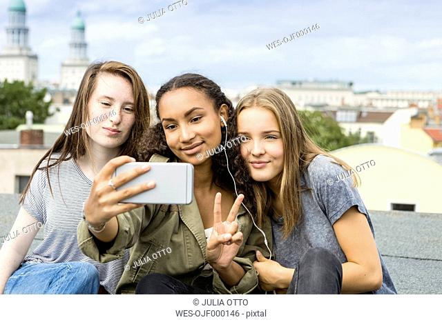 Germany, Berlin, three teenage girls sitting on roof top taking selfie with smartphone