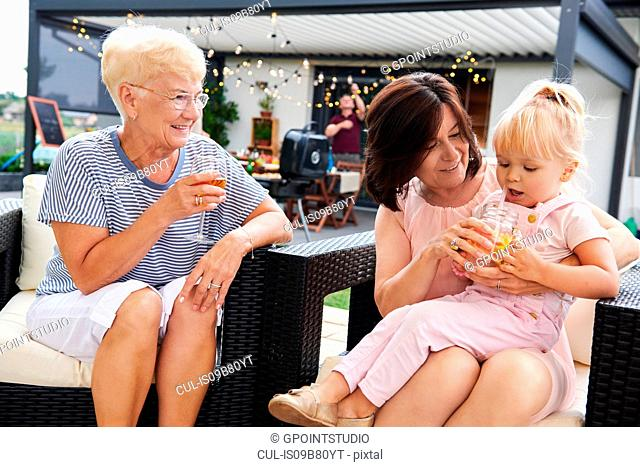 Senior and mature women with female toddler on lap at family lunch on patio