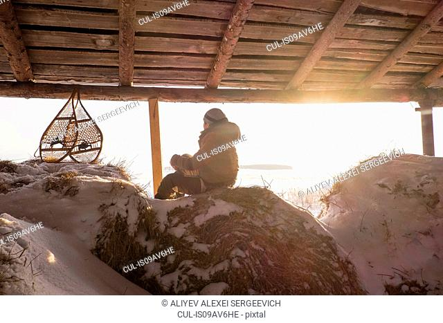 Man sitting on snowy haystack in barn with snow shoes, Ural, Russia