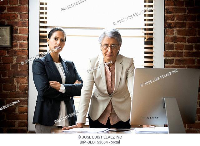 Hispanic businesswomen standing at office desk