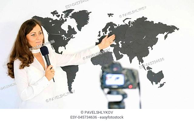The journalist is reporting on the background of a large map of the world in front of the camera