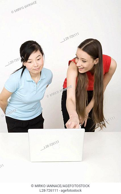 Two young businesswomen using laptop at desk