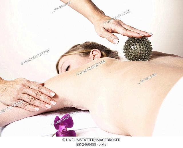 Young woman being massaged on the back with a spikey rubber massage ball