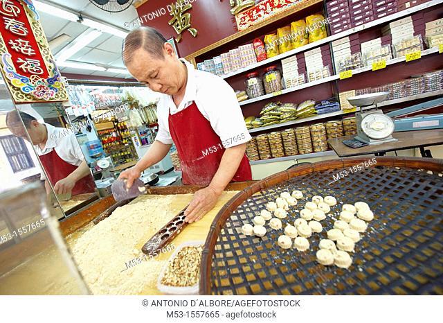 A man making traditional almond biscuits in a workshop located in Rua Da Felicidade  Macau  China