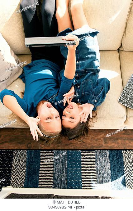 Girls upside down on sofa using digital tablet to take selfies