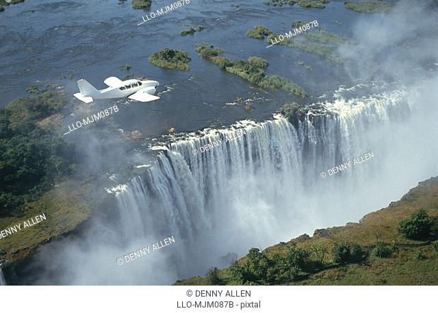 Small aeroplane flying over Victoria Falls, Zimbabwe