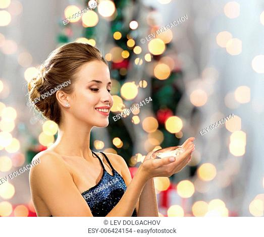 people, holidays and glamour concept - smiling woman in evening dress with diamond over christmas tree lights background