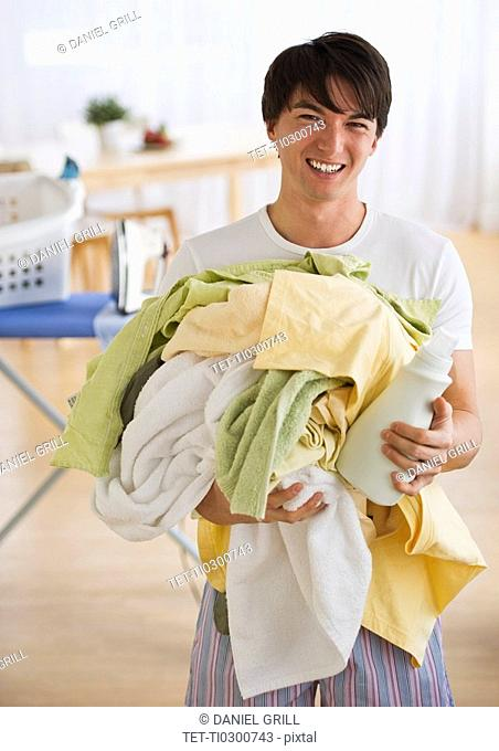 Man holding pile of laundry
