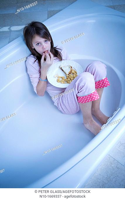 Preteen girl eating lunch in a bathtub