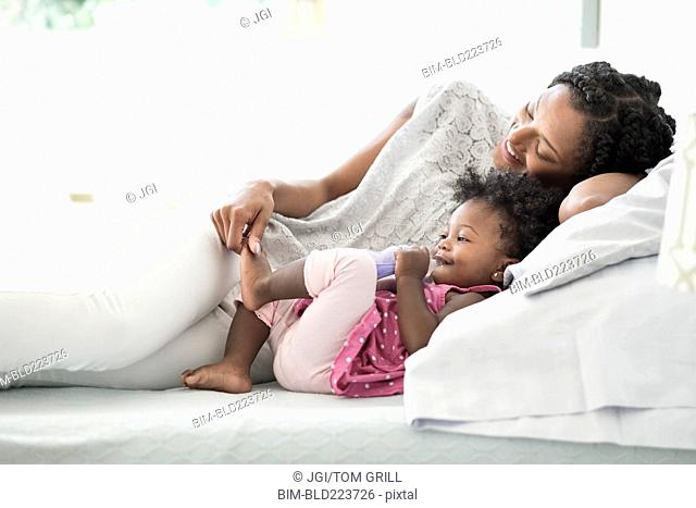 Black woman playing with foot of baby daughter on bed
