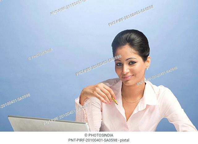 Businesswoman working on a laptop and smiling
