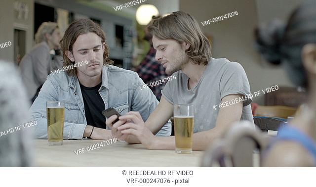 Men drinking beer and talking with each other while sitting in pub