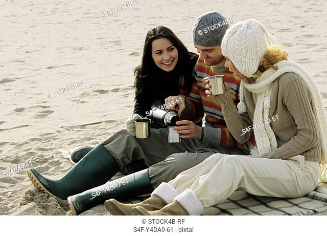 Man poring Tea into a Woman«s Cup from a Thermos Flask - Friends - Gesture - Trip - Beach - Beverage - Season