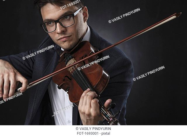 Handsome man wearing formals playing violin against black background