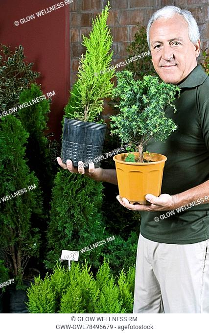 Man holding potted plants in a greenhouse