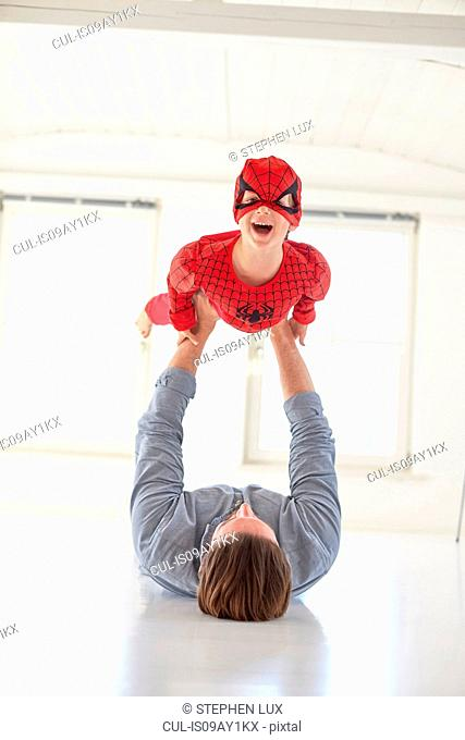 Father lying on floor holding up son wearing superhero costume