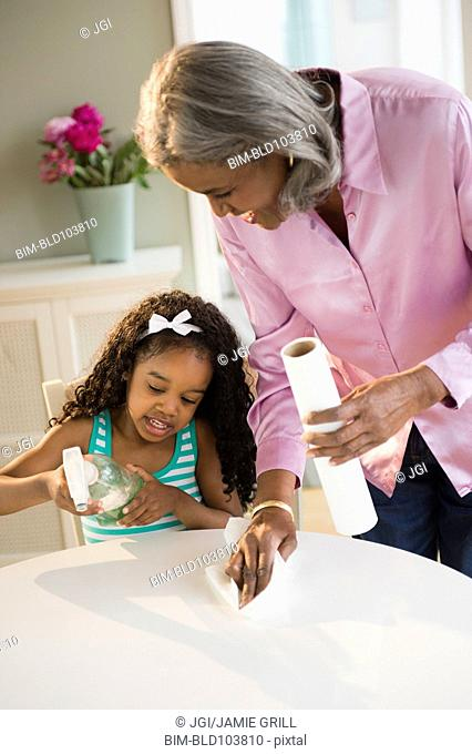 African American grandmother and granddaughter cleaning the table
