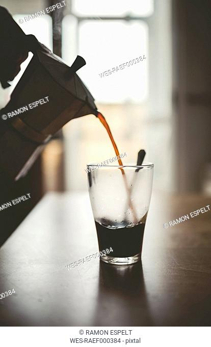 Man pouring espresso from can into a glass