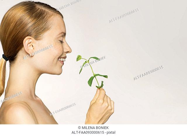 Young woman enjoying fragrence of fresh mint leaves