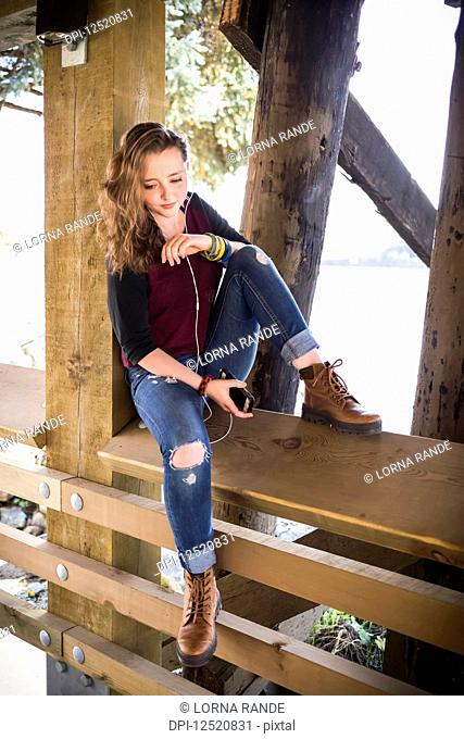 A young woman sitting on a wooden railing under a bridge by water listening to music; New Westminster, British Columbia, Canada