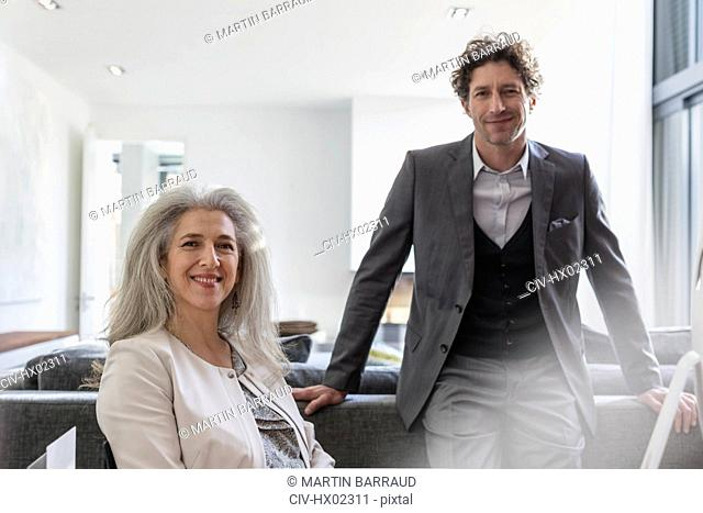Portrait confident businessman and businesswoman in living room