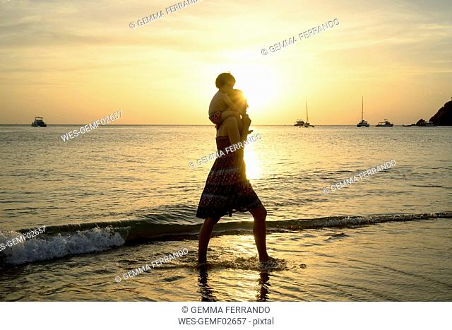 Thailand, Koh Lanta, silhouette of mother with baby girl on her shoulders at seashore during sunset