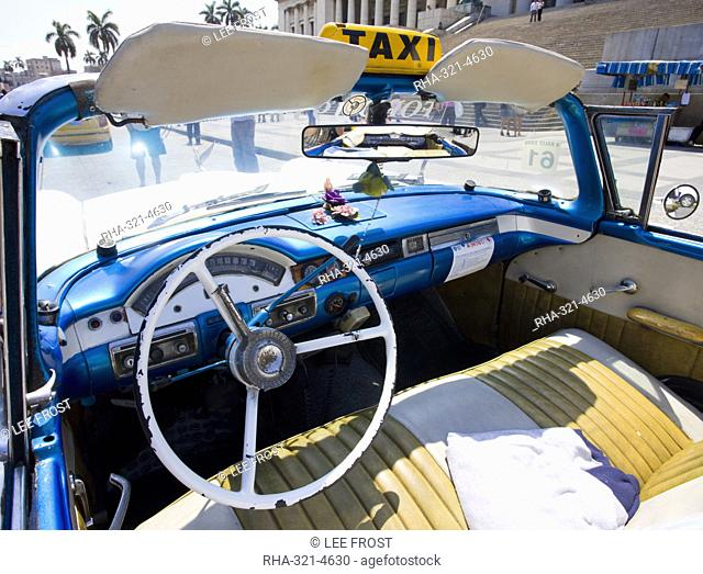 Interior of old American car being used as a taxi showing blue dashboard, original steering wheel and leather seats, parked outside The Capitolio, Havana, Cuba